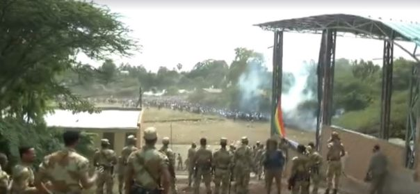 A screenshot from video posted to Facebook by Jawar Mohammed of the Irreecha stampede, in which security forces look on as people run away. Shots can be heard as smoke rises from the scene.